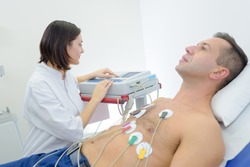 doctor is performing an electrocardiography