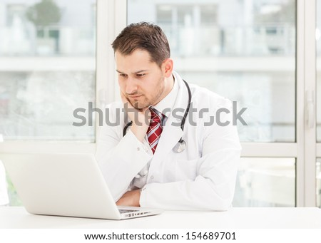 Doctor is sitting at his desk with notebook
