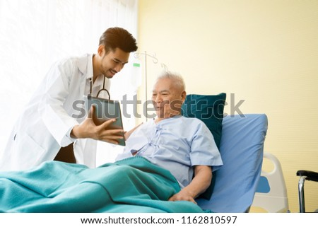 Doctor is standing by to explain the treatment information via the tablet to an elderly patient lying in bed in a private sickroom. The treatment program is suitable for people to socialize elderly.
