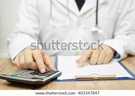 Doctor is using calculator to sum all of expenses