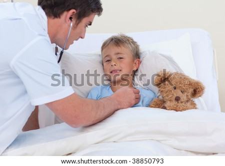 Doctor listening to a child breath with stethoscope in bed