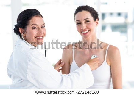 Doctor listening to patients chest with stethoscope in medical office