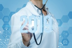 Doctor listens to 2019 figures on a blue background. Concept of a new year.