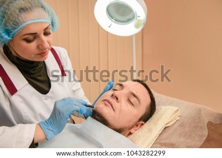 Doctor makes pencil contours on patient #1043282299