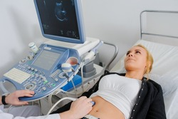 Doctor makes the patient women abdominal ultrasound. Ultrasound Scanner in the hands of a doctor. Diagnostics. Sonography