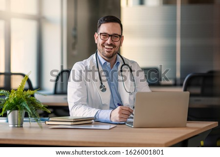 Doctor man sitting at the desk at his working place and smiling at camera. Perfect medical service in clinic. Happy future of medicine and healthcare. Happy doctor looking at camera
