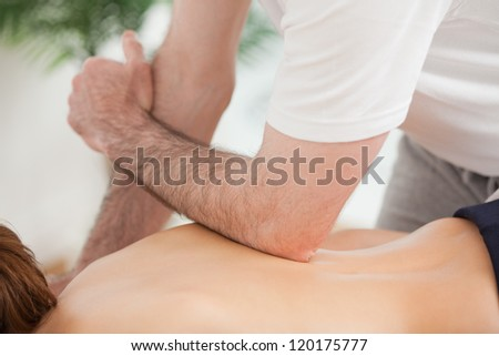Doctor massaging his back of his patient while using his elbow in a room