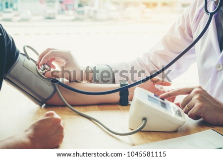 Doctor Measuring arterial blood pressure woman patient on right arm Health care in hospital #1045581115