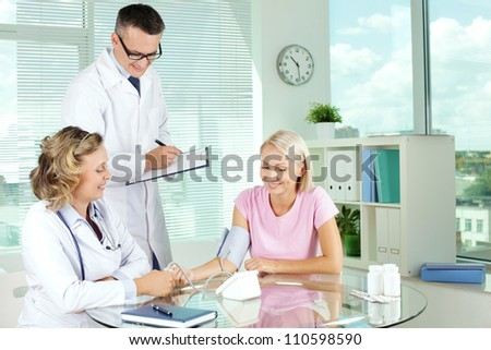 Doctor measuring blood pressure of patient at medical consultation