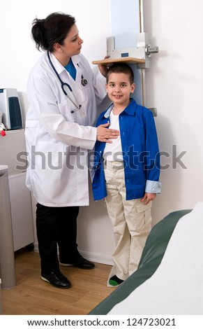 Doctor measuring little child boy height growth at clinic.