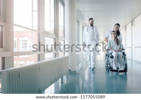 Doctor, nurse, and patient in wheelchair walking on hospital corridor