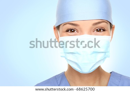 Doctor / nurse smiling behind surgeon mask. Closeup portrait of young asian caucasian woman model in blue medical scrub.