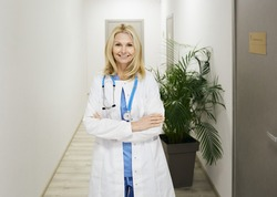 Doctor occupation. Middle-age general practitioner with phonendoscope stands in medical clinic corridor