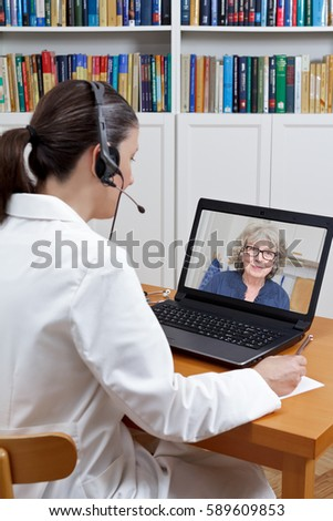 Doctor of geriatrics sitting at the desk of her office with headset and laptop, talking to an old patient via the internet, telehealth concept