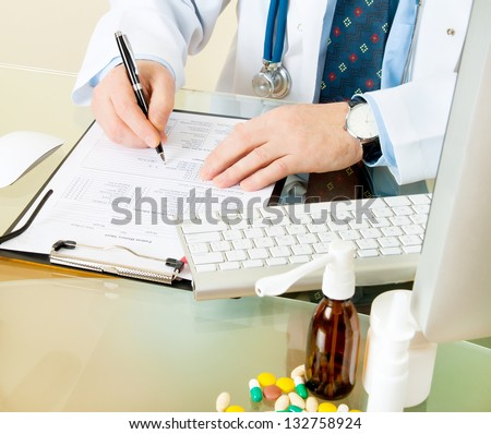 Doctor on his workplace with computer, pills, tablets, write a prescription patient data history