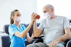 Doctor or nurse caregiver exercise with senior man, both wearing protective masks,  at home or nursing home