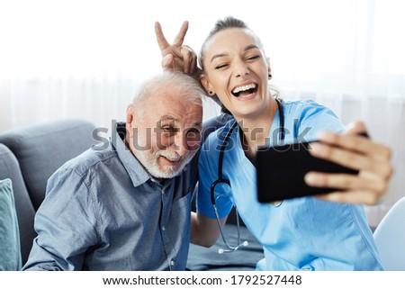 Doctor or nurse caregiver helping senior man with a mobile phone taking selfie at home or nursing home