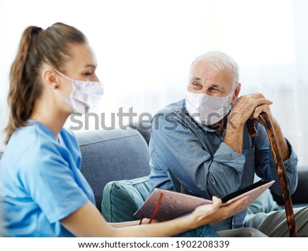 Doctor or nurse caregiver with senior man wearing protective masks looking at photo album and picture  at home or nursing home
