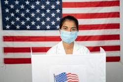 Doctor or nurse coming to polling booth with medical mask wearing for voting - concept of US election, in person voting showing with US flag as background