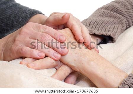 Doctor or nurse holding elderly wrinkled hand