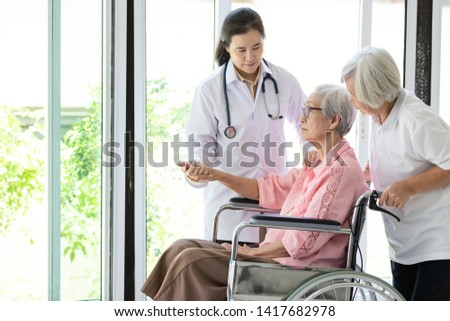 Doctor or nurse supporting disabled,alzheimer senior asian woman on wheelchair,female caregiver,elderly patient with depressive symptoms need close care,healthcare,depression concept