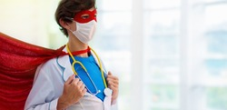 Doctor or nurse wearing surgical face mask in superhero cape. Medical staff during coronavirus outbreak. Super hero power for clinic and hospital personal.