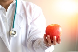 Doctor or nutritionist hold an apple. Good medical healthcare nutrition concept. An apple a day keeps the doctor away