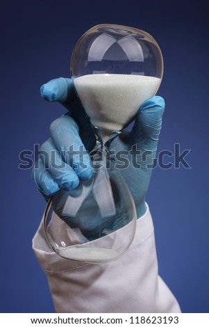 Doctor or surgeon holding an hourglass concept for long delays for medical procedure and hospital waiting list