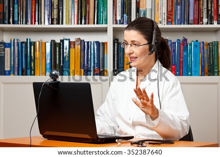 Doctor or vet sitting with a headset or headphones at her desk in front of a computer with an attached camera, talking soothingly with a patient, telemedicine concept