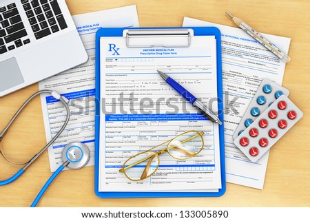 Doctor paperwork, medical healthcare and insurance concept: clipboard with prescription medicine drug claim form, office laptop, stethoscope, eyeglasses, blue pen and thermometer on wooden table