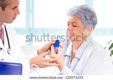Doctor performs treatment to an old woman with inhaler.