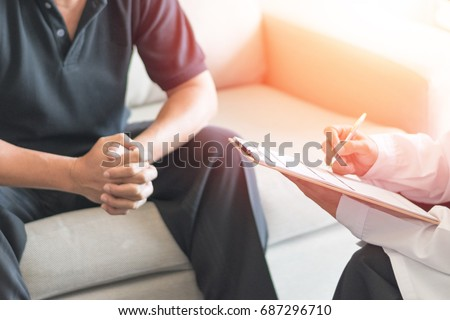 Doctor physician consulting with male patients in hospital exam room. Men's health concept.