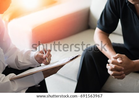 Doctor physician consulting with male patients in hospital exam room. Men's health concept. #691563967