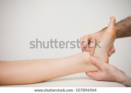 Doctor placing his fingers on the foot of a patient in a room