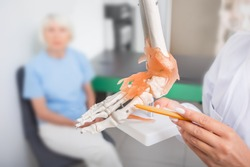 Doctor points to the anatomical model of the foot. Arthritis, foot injuries and pain. physiotherapy and orthopedic