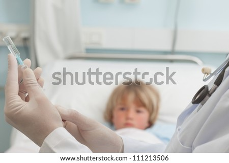 Doctor preparing a syringe in front of a child in hospital ward
