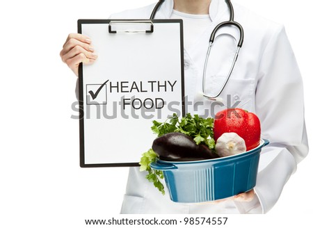 "Doctor prescribing healthy natural food; closeup of doctor's hands holding clipboard with marked checkbox ""Fresh vegetables"" and brazier with vegetables; healthy eating concept isolated on white"