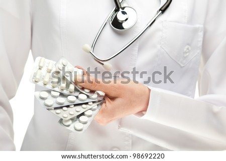 Doctor prescribing many pills; closeup of doctor's hand holding many medicines