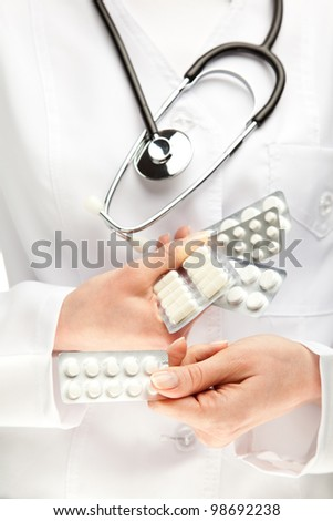 Doctor prescribing many pills; closeup of doctor's hands holding many medicines