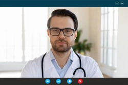 Doctor provides distant consultation to patient by video call, share useful info about corona virus pandemic infection outbreak concept. Head shot therapist, laptop telecommunications app screen view