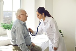 Doctor putting stethoscope on patient chest listen heartbeat and lungs breath. Elderly male person exam at hospital ward. Cardiologist physician appointment. Nursing home clinic service for pensioner