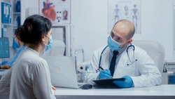 Doctor questioning patient during covid-19 pandemic, writing answears in clipboard. Medical consultation in protective equipment concept shot of sars-cov-2 global health pandemic crisis