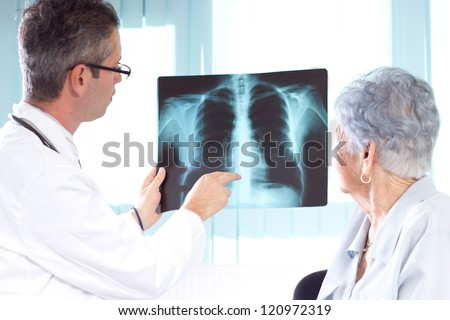 Doctor Reviewing X-rays. Doctor explaining diagnosis to his female senior patient.