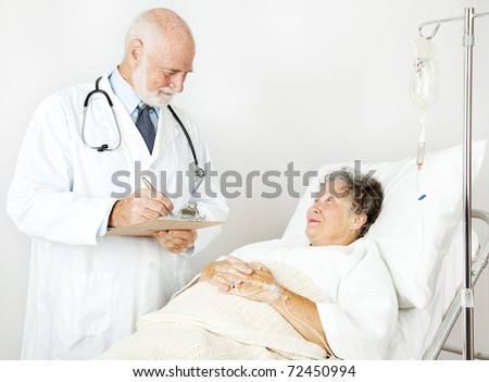 Doctor reviews his hospital patient's medical history, taking notes.