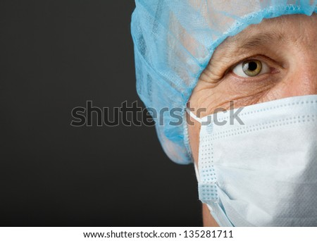 Doctor's face with mask and cap on grey background