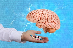 doctor's hand holds out medicines, human brain model, medical health concept, intellectual disability, study of the activity of the cerebral cortex, psyche and consciousness