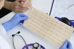 Doctor's hands hold result of the cardiogram next to patient sitting. Examination of the cardiovascular system concept.