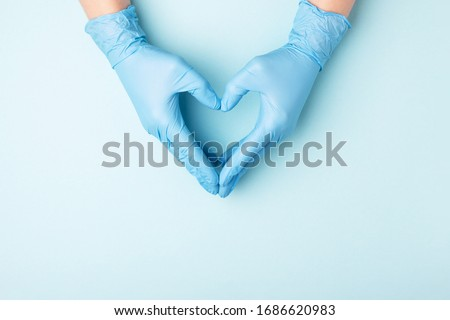 Photo of  Doctor's hands in medical gloves in shape of heart on blue background with copy space.