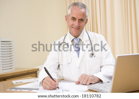 doctor sat at office desk smiling