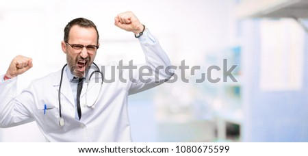 Doctor senior man, medical professional happy and excited celebrating victory expressing big success, power, energy and positive emotions. Celebrates new job joyful at hospital #1080675599